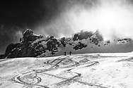 Two ski tourers in a storm and snow drift are climbing up to mount Glatten, Muotathal, Schwyz, Switzerland