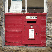 Red Mail box in  a stone wall in the old post office in Ballinluig, Perthshire, Scotland<br />
