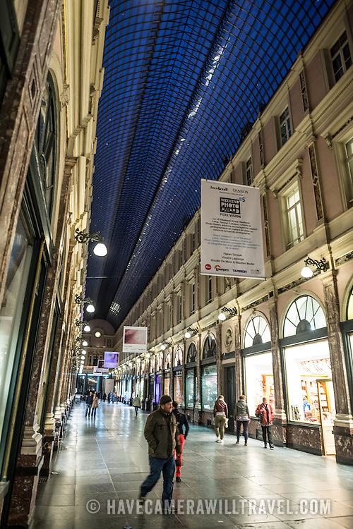 A night shot of Galeries St-Hubert, an historic luxury shopping arcade in the Lower Town of Brussels with a distinctive glass roof.