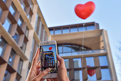 "© Licensed to London News Pictures. 15/02/2018. LONDON, UK.  London, UK.  15 February 2018.  A woman photographs a giant chubby heart balloon outside Bloomberg's HQ in Queen Victoria Street during ""Chubby Hearts Over London"", a design project conceived by Anya Hindmarch.  Supported by the Mayor of London, the British Fashion Council and the City of Westminster giant chubby heart balloons will be suspended over (and sometimes squashed within) London landmarks as a declaration of love to the city starting on Valentine's Day and continuing throughout London Fashion Week.  Photo credit: Stephen Chung/LNP"