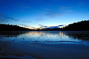 Sunset with moon over first ice on the Vermilion River in Northern Ontario, Canada.