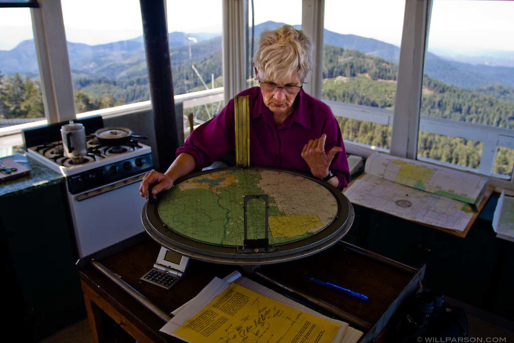 The keeper of the Tobias Peak Fire Lookout examines a map of the surrounding Sequoia National Forest.