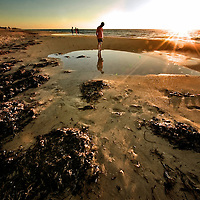 A young man looks at his reflection in rock pool in Busselton Beach Australia