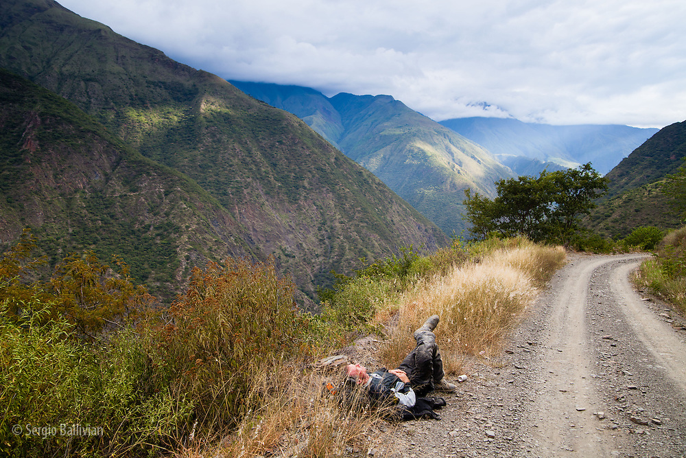 Bill Dragoo takes a nap on the side of the road near his Suzuki DR 650 adventure motorcycle in the semi-tropical Yungas valleys of Bolivia's Andes mountains.