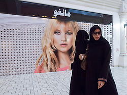 Arab women walk past western fashion billboard in upmarket Villaggio shopping mall in Doha Qatar