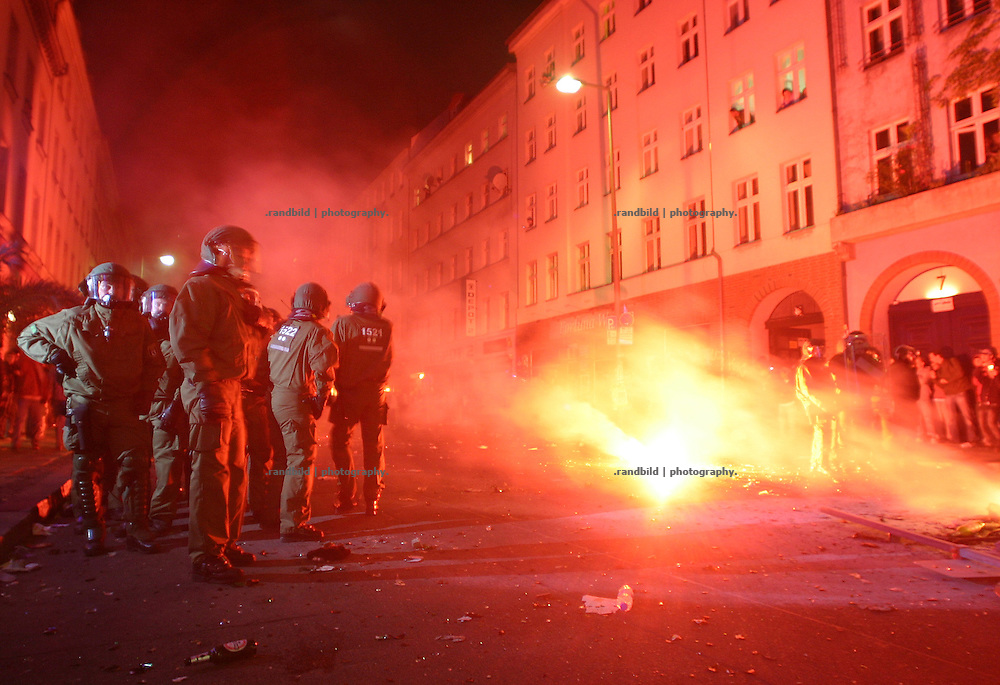 Am 1.Mai stehen Polizisten in Kreuzberg, während auf der Straße Protestfeuer brennen. Policemen stands beside burning fires on the street during the 1.May riots