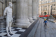"A child plays on the steps in front of Ecce Homo - Kate Allen, Director of Amnesty International UK, helped by Canon Mark Oakley (Chancellor of St Paul's Cathedral), installs Mark Wallinger's 'Ecce Homo' statue at St Paul's Cathedral. The life-size sculpture shows the figure of Jesus Christ and was the first artwork to be shown on Trafalgar Square's fourth plinth in 1999.Mark Wallinger, who won the Turner Prize in 2007, said: ""This vulnerable figure will stand at the top of the steps outside the entrance to St Paul's Cathedral as we approach Easter to highlight the plight of people around the world who are imprisoned and whose lives are threatened for speaking the truth, and for what they believe."""