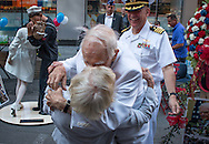 In New York City's Times Square on August 14, 2014, on the 69th anniversary of the end of the war, WWII vet Sydnor Thompson, 90, reenacts the famous kiss with his wife, Harriette, 91, both of Charlotte, NC, in front of the just unveiled sculpture of the kiss. Their son, US Navy Chaplain Sydnor Thompson Jr. looks on.