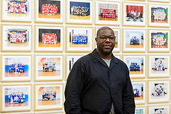 "© Licensed to London News Pictures. 11/11/2019. LONDON, UK. Turner Prize-winning artist and Oscar-winning filmmaker Steve McQueen poses at the preview of ""Year 3"", his new exhibition at Tate Britain.  The artwork comprises 3,128 traditional school class photographs of Year 3 pupils from 1,504 of London's primary schools.  The work reflects a picture of the present and is on display 12 November to 3 May 2020.  Photo credit: Stephen Chung/LNP"