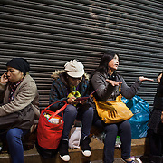 A group of Filipino women sit and chat and eat in the streets in Hong Kong Central on a Sunday evening. Hong Kong has a huge Filipino population, most of them women working as domestic servants. They meet in public on their days off since none of them have their own private accomodation. 7 million people live on 1,104km square, making it Hong Kong the most vertical city in the world.
