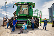"06 AUGUST 2020 - FAIRFIELD, IOWA: People use the shade of a combine that was being auctioned off to watch the bidding during the auction on the Adam Farm near Fairfield. Gary Adam, 72 years old, has been farming in the Fairfield area since 1971. He decided to retire this year because he wants to travel and because it's so difficult to make money in farming this year. He said he wants to ""shed the risk and responsibility. If things were super good, like they were 2006-2012, I might stay in it, but they're not."" An increasing number of farmers in the Midwest are retiring this year as it becomes harder to make money on crops. In addition to low prices, Iowa farmers are being hit with a drought this year, with well below average rain over most of the state. Because of the COVID-19 pandemic, the auction on Adam's farm was one of the first live in person auctions since winter. Most auctions are now done on line.    PHOTO BY JACK KURTZ"