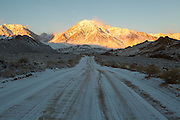 Snowy Buttermilks Road leads up to Mount Tom, illuminated by the early morning light. January 2011.
