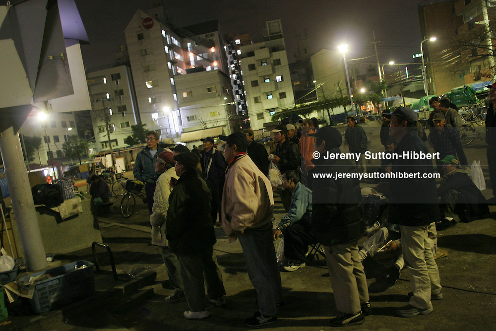 Unemployed homeless men living rough in the Sankaku Park area of Kamagasaki watch a television for entertainment, near Osaka, Japan. Approximately 8,000 homeless people live in Osaka City, with 20,000 attending the day labour market in search of daily employment.