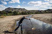 RADIUM SPRINGS, NM - APRIL 10, 2015:  Oscar Escapita nets minnows on the trickle that is the Rio Grande. The Rio Grande runs nearly dry as the Elephant Butte Reservoir is refilled upstream. CREDIT: Max Whittaker for The New York Times