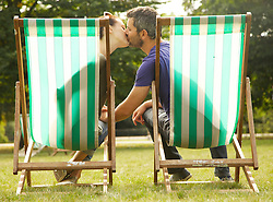 Couple Sitting on Deck Chairs Kissing, St. James's Park, London, England, Rear view