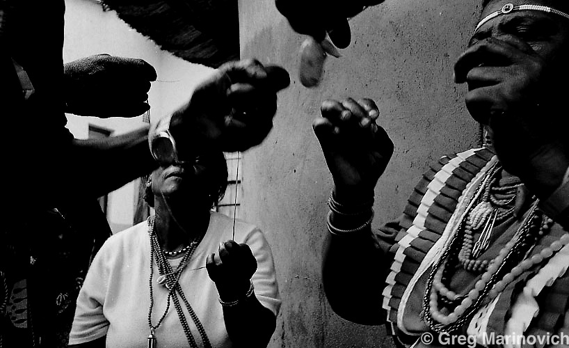 Sangoma initiates in the MonTau (VanDau) or alien spirit cult, perform tasks during their graduation to prove they have mastered the powers and are spirit mediums and may become sangomas in Magasoa or Magnetized village, in the Sekhukhune district of Limpopo, January 10, 2009. The graduation of these Pedi mediums was a communal event, with the traditional sortghum beer being drunk by many relatives and villagers. The sangoma trainer is the dreadlocked man - Frans Makunyane, his assistnt is a sangoma from Tafelkop, next to Groblersdal called Peter Benjamin Mohlala - crawls on final day. The overseeing samgomas are Frans' mother, Enika Kgoga and also the elderly man with beads. Photo: Greg Marinovich.