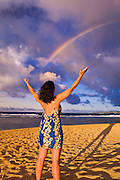 Celebrating rainbows at sunset on Tunnels Beach, Island of Kauai, Hawaii USA