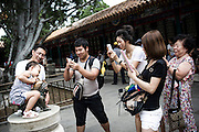 A Chinese family takes a picture of their son at the Summer Palace in Beijing, China, July 21, 2014.<br /> <br /> Smartphones are an essential tool of Chinese ordinary life. Everywhere in China, people use them to take pictures to share online, to talk and chat, to play videogames, to get access to the mainstream information, to get connected one each other. In the country where the main global social media are forbidden - Facebook, Twitter and Youtube are not available  -, local social networks such as WeChat have a wide spread all over the citizens. The effect is an ordinary and apparently compulsive way to get easy access to digital technology and modern way of communication. <br /> A life through the display. Yes, We Chat.<br /> <br /> © Giorgio Perottino