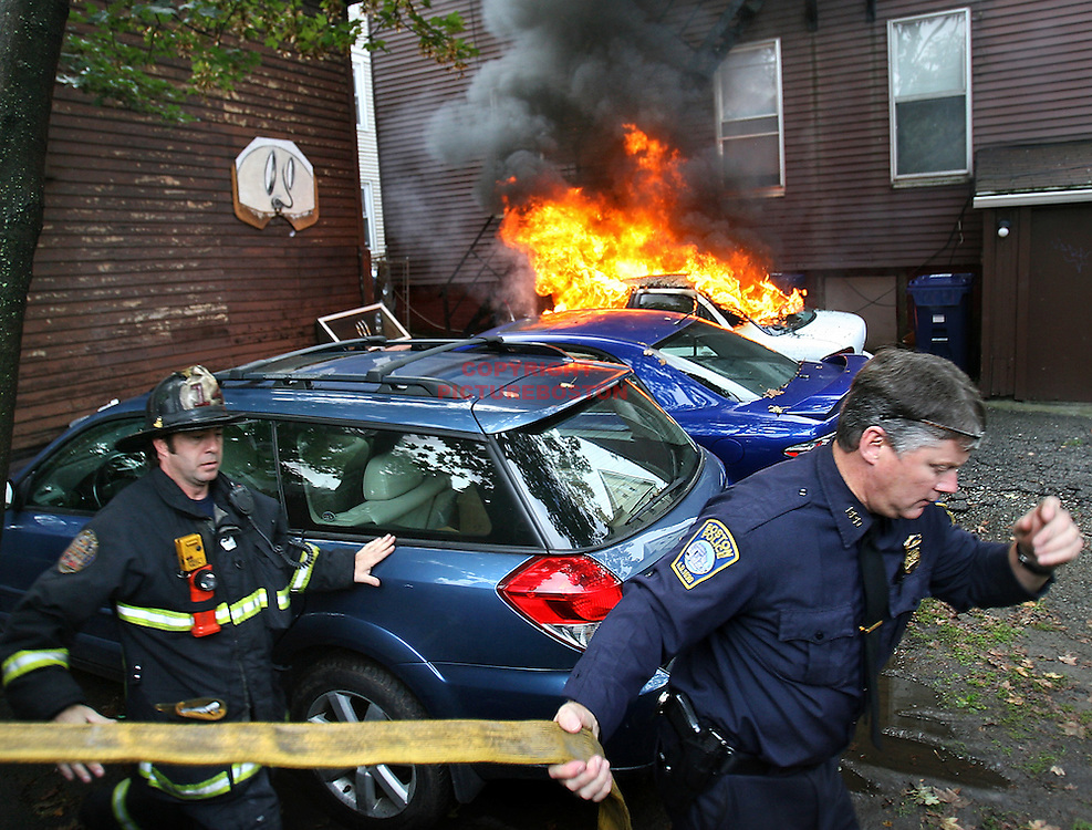 Boston police arson detective James Freeman helps stretch a fire hose toward a burning car, one of five cars in the Pratt street area of Allston, that were all lit this morning, September 24, 2011. Freeman was on the scene investigating the other 4 suspicious fires when neighbors ran toward officials and told them there was another fire down the street.  Staff Photo by Mark Garfinkel  .