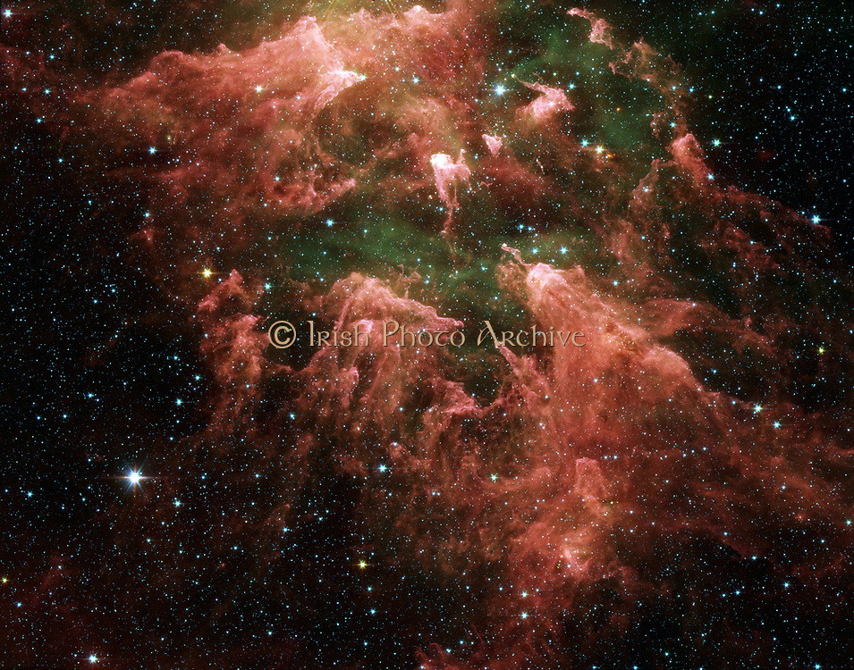 This false-color image taken by NASA's Spitzer Space Telescope shows the 'South Pillar' region of the star-forming region called the Carina Nebula. Though the nebula's most famous and massive star, Eta Carinae, is too bright to be observed by infrared telescopes, the downward-streaming rays hint at its presence above the picture frame. Ultraviolet radiation and stellar winds from Eta Carinae and its siblings have shredded the cloud to pieces, leaving a mess of tendrils and pillars. This shredding process triggered the birth of the new stars uncovered by Spitzer. This image was taken by the infrared array camera on Spitzer. It is a three-color composite of invisible light, showing emissions from wavelengths of 3.6 microns (blue), 4.5 microns (green), 5.8 microns (orange), and 8.0 microns (red).