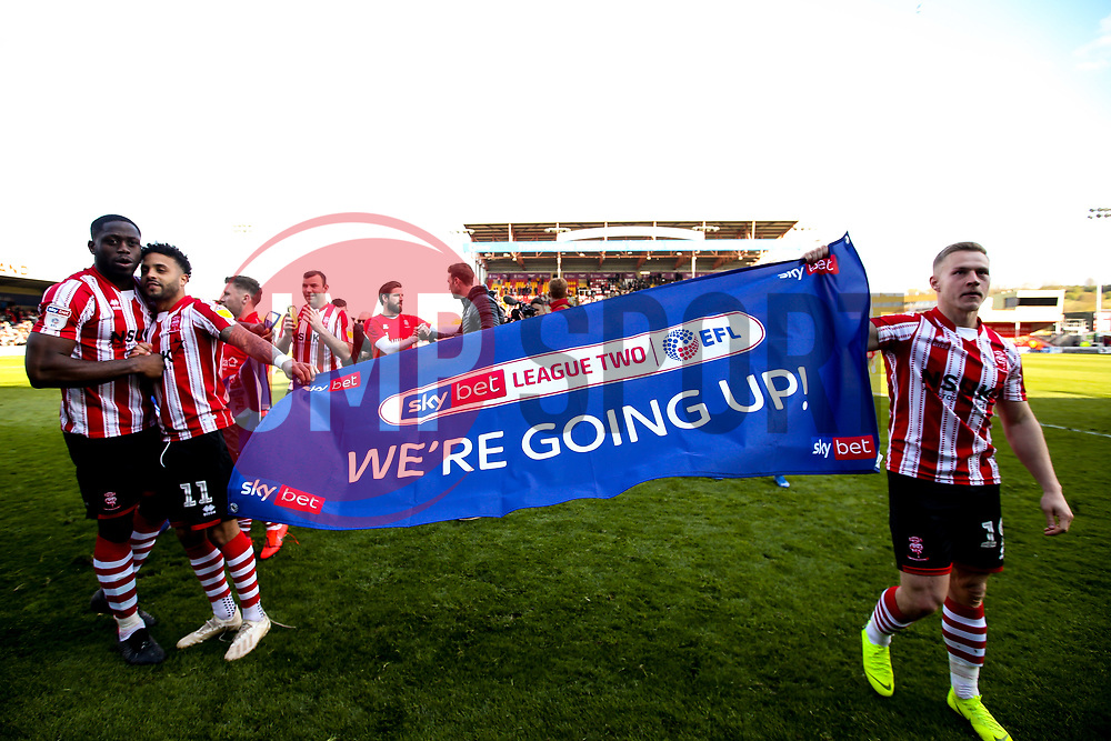 John Akinde, Bruno Andrade and Danny Rowe of Lincoln City celebrate winning promotion from Sky Bet League Two to Sky Bet League One - Mandatory by-line: Robbie Stephenson/JMP - 13/04/2019 - FOOTBALL - Sincil Bank Stadium - Lincoln, England - Lincoln City v Cheltenham Town - Sky Bet League Two
