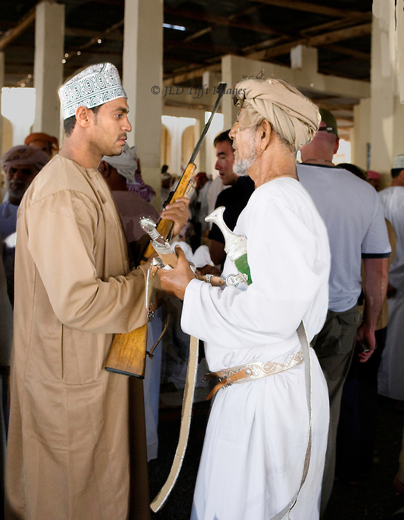 Market day in the Sinaw souk, Oman.  Livestock (goats, camels), vegetables, and weapons on offer.  Men and women shoppers. Two men negotiate the sale and purchase of a rifle.