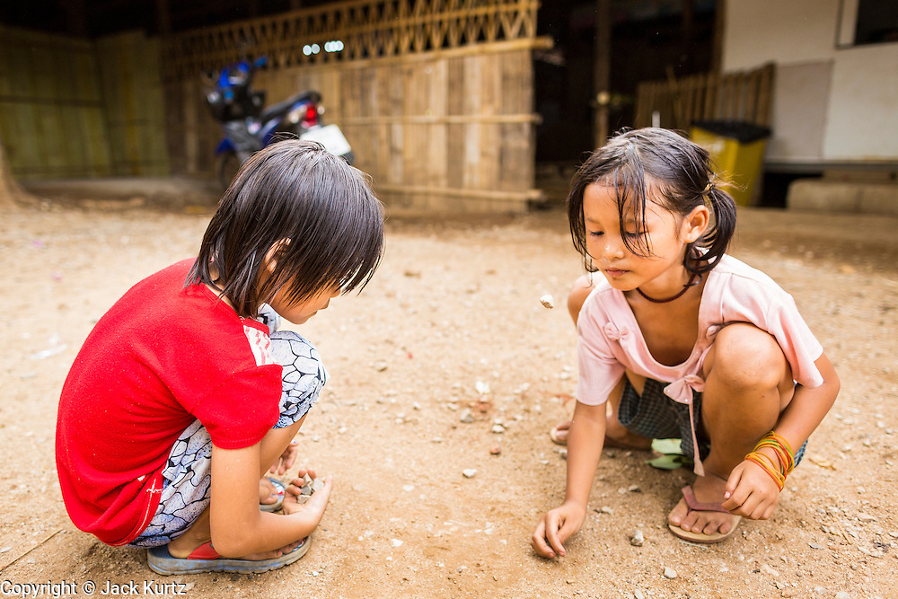 "22 MAY 2013 - MAELA REFUGEE CAMP, TAK, THAILAND: Burmese refugee children play a Burmese version of ""jacks"" with rocks in Mae La Refugee Camp. Mae La (Maela) is the largest refugee camp for Burmese in Thailand. Over 90% are ethnic Karen. It was established in 1984 in Tha Song Yang District, Tak Province in the Dawna Range area and currently houses 40,000 refugees. The Thai government has indicated that it would like to close the camp and repatriate the refugees to Myanmar as soon as the political situation in Myanmar is stable enough.   PHOTO BY JACK KURTZ"