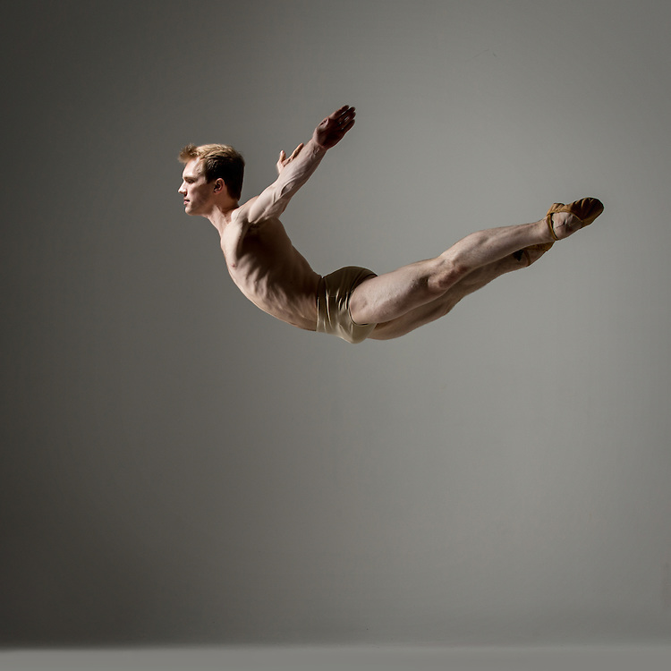 Male dancer jumping in the nude, taken in the photo studio on a grey background. Photograph taken in New York City by photographer Rachel Neville.