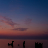 Remains of an old pier, a cresent moon, and morning twilight over the Delaware Bay, Port Mahon, DE