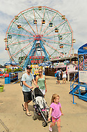 Brooklyn, New York, USA. 10th August 2013. Parents are pushing a stroller while thier young daugher walks ahead at Luna Park, with the Wonder Wheel in the background, during the 3rd Annual Coney Island History Day celebration.