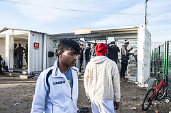 October 27, 2016 - Calais, France - LEs young refugees access the CAP with their palm prints, in Calais, October 27, 2016..The Calais jungle begins its fourth day of dismantling. Most refugees have left the jungle. Some roam the jungle and over 100 young refugees have no place in the Provisional Home Centre. The workers are destroying the jungle growing rapidly. (Credit Image: © Julien Pitinome/NurPhoto via ZUMA Press)