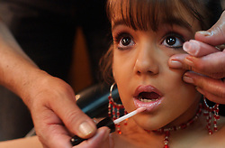 A contestant gets her makeup applied during the Miss Mini Universe competition for children ages 6-10.  Venezuela has a deep culture of beauty, fashion and sex appeal. There are dozens of beauty pageants throughout the year for boys and girls of all ages..