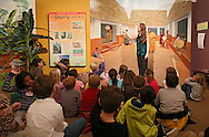 Lynn Koos, Curator, talks to students from Westfield Elementary School about items in a painting in the Western Africa exhibit at the African American Museum of Iowa in Cedar Rapids on Friday, March 22, 2013.