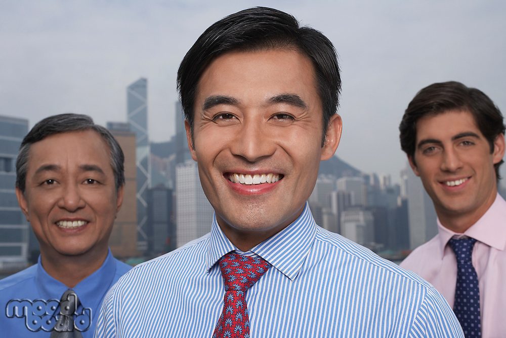 Portrait of three business men office building in background