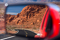 Side view mirror displays the fiery red rock formations of Valley of Fire State Park in Nevada, USA.