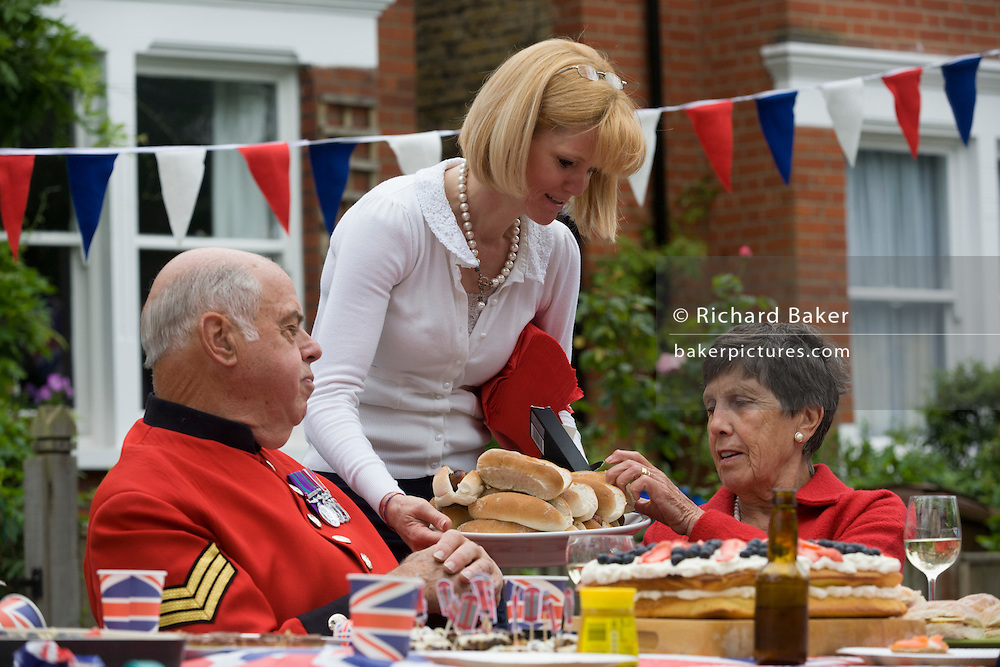 Serving the elderly (including a visiting Chelsea Pensioner) at a community street party in Dulwich, south London celebrating the Diamond Jubilee of Queen Elizabeth. A few months before the Olympics come to London, a multi-cultural UK is gearing up for a weekend and summer of pomp and patriotic fervour as their monarch celebrates 60 years on the throne and across Britain, flags and Union Jack bunting adorn towns and villages.