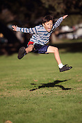 Happy boy jumping in the park - authentic action - copy space bottom