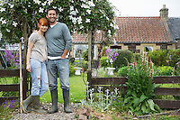 Couple standing outside house in countryside portrait