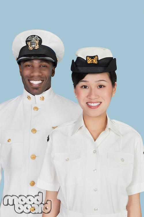 Portrait of multi-ethnic US Navy officers smiling over light blue background