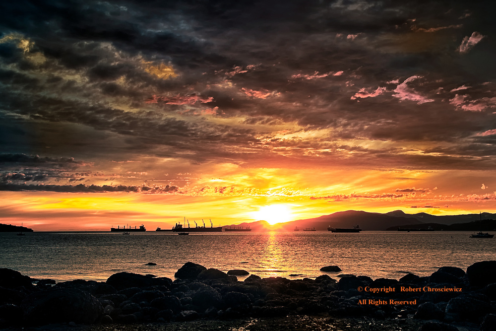 Spring Sunset - Kits Beach: A fiery orange sunset colours a cloudy sky, as seen from Kitsilano Beach, Vancouver British Columbia, Canada.