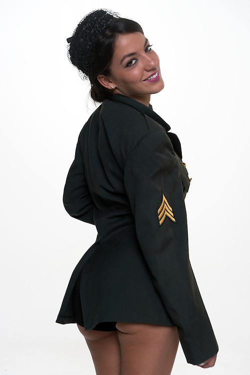 Woman in military uniform showing back and smiling at camera