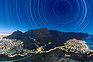 Star Trails above Table Mountain in Cape Town, South Africa. Photographed by Eric Nathan over a period of 8 hours on the night of 11/12 June 2014. This image comprises over 900 30-second exposures shot in RAW and then layered in post to render the star trails. The landscape is illuminated by the light of the (almost) full moon and the star trails form concentric circles around the south celestial pole.