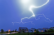 A powerful bolt of lightning appears to hover over a row of houses. This midsummer thunderstorm lasted 6+ hours and produced lots of similar lightning bolts.<br />