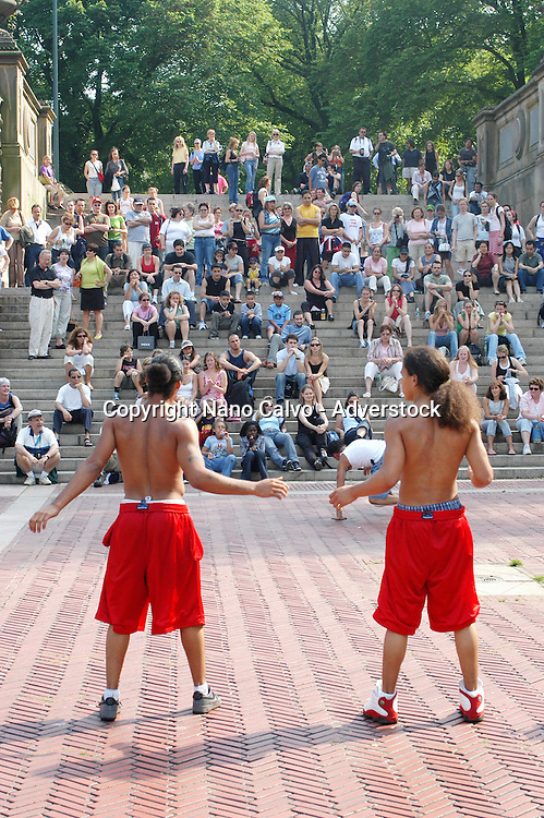 Two young men doing an acrobatics spectacle in front of an improvised audience, in Central Park, New York