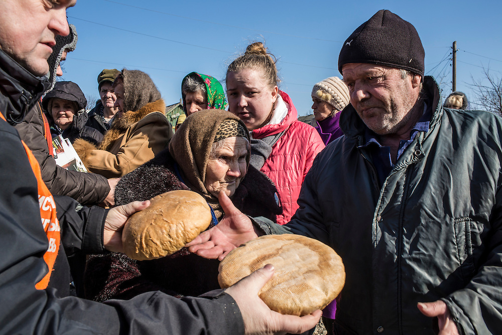 MARIINKA, UKRAINE - FEBRUARY 20, 2016:  Local residents receive bread distributed as humanitarian assistance by volunteers affiliated with the Christian Help Center of the Church of the Transfiguration in Mariinka, Ukraine. The Donetsk suburb has been the scene of some of the heaviest fighting recently between Ukrainian forces and pro-Russian rebels. CREDIT: Brendan Hoffman for The New York Times