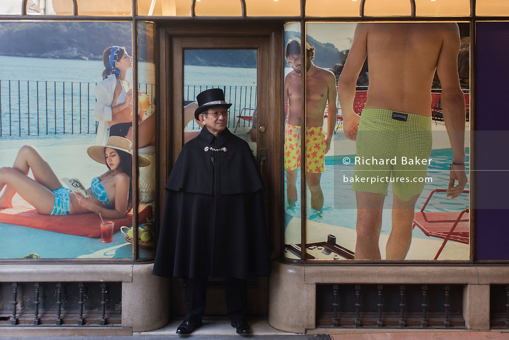 A cloaked guide stands surrounded by a younger generation in beachwear, on a poster background in Burlington Arcade in central London. The pedestrian arcade, with smart uniform shop fronts under a glazed roof, has always been an upmarket retail location. It is patrolled by Burlington Arcade Beadles in traditional uniforms including top hats and frockcoats. The original beadles were all former members of Lord George Cavendish's regiment, the 10th Hussars.