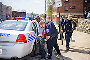 Baltimore, Maryland - April 21, 2015: A man who ran from police, through the same walkway Freddie Gray was arrested two Sundays ago, is detained in the back of a police cruiser. Gray, 25 died from injuries sustained while in police custody in the back of a police van. Gray's spine was reportedly 80% severed.<br /> <br /> CREDIT: Matt Roth for The New York Times<br /> Assignment ID: 30173645A