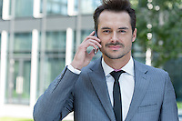 Portrait of confident businessman using cell phone outside office