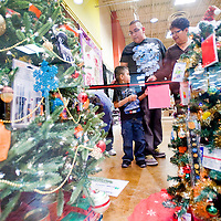 120412       Cable Hoover<br /> <br /> Florina Shetima, right, Jonathan Besselente and Malcolm Kaskalla decide which tree raffle to enter at the Festival of Trees in Gallup's Rio West Mall Tuesday.