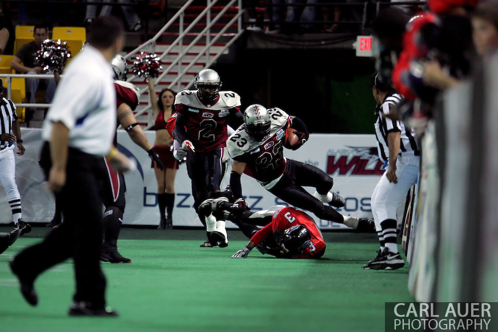 6-28-2007: Anchorage, AK - Donny Delaney (23) of Alaska has his legs knocked out from under him by  Barracuda Olan Coleman in the Alaska Wild 47 to 53 loss to the CenTex Barracudas at the Sullivan Arena...